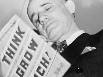 "Napoleon Hill holding his book ""Think and Grow Rich"""